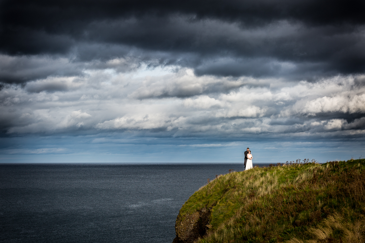 Groom with her Bride Standing by a Cliffside Landscape Wedding Photography Scotland